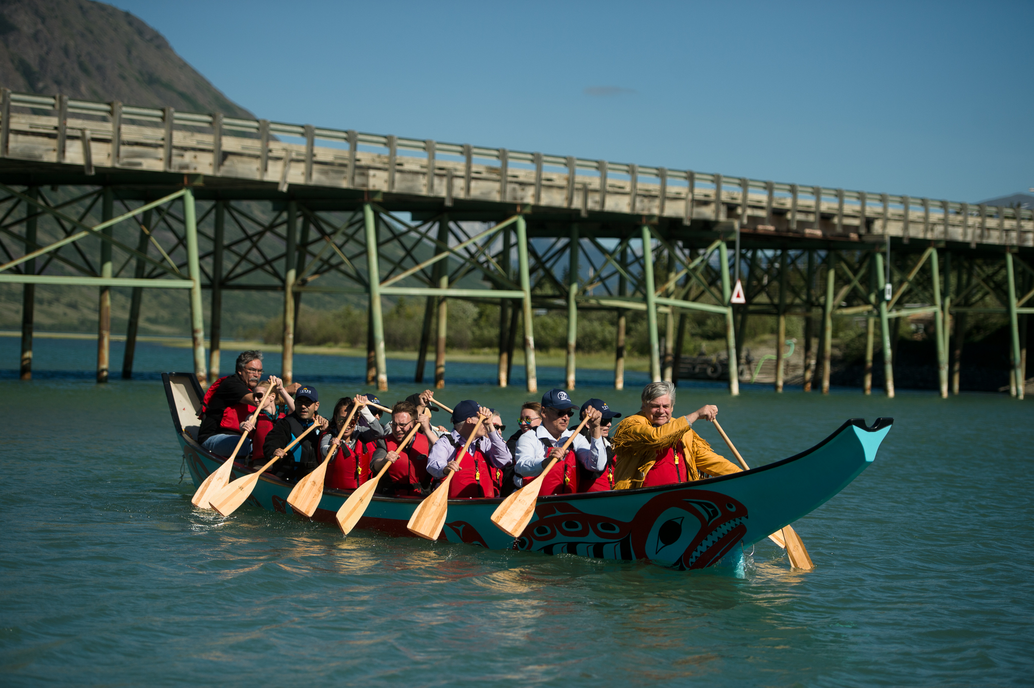 First Nation, federal and territorial leaders paddle a Tlingit boat in Carcross during the Council of Yukon First Nations General Assembly. (Photo: Alistair Maitland)
