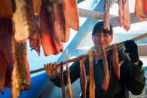 Persis Hager prepares fish at the Na-cho Nyak Dun fish camp at Fraser Falls on the Stewart River. This is an important place for citizens to learn about traditional ways of survival. (Photo: Frits Meyst)