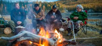 Elder Betty Lucas shares stories and knowledge around the fire on the banks of the Stewart River. (Photo: Frits Meyst)